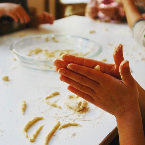 Mani di bimba che fanno la pasta fresca