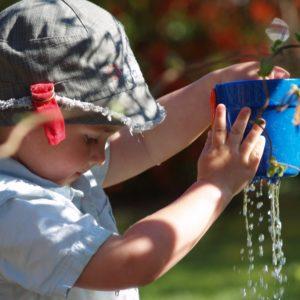 Bambino che gioca con secchiello pieno d'acqua